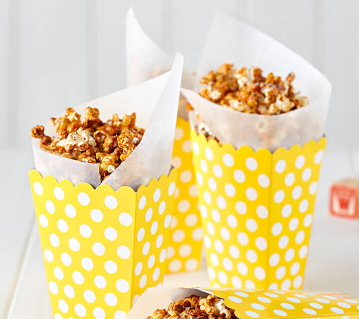 Caramel spiced popcorn in a yellow and white polkadot container